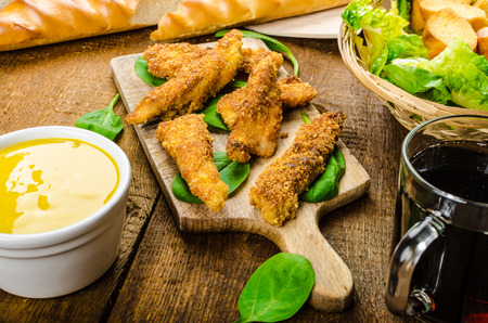 Corn crusted Chicken Tenders with spinach and toast, honey-dijon mustard dip, homemade bread baguette photo