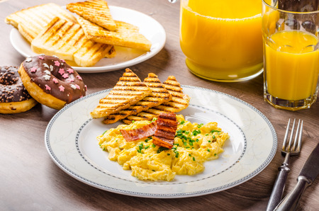 breakfast plate: Scrembled eggs with panini toast and donut, fresh orange juice for sure and healthy