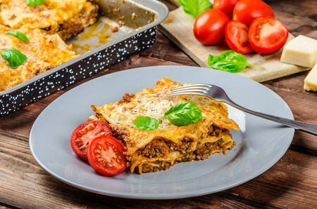 Lasagna bolognese, beef, parmesan, Italian classic, simple serving, wood board photo