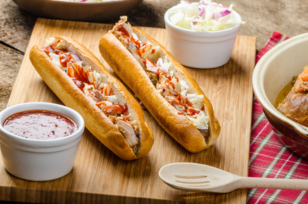 sause: Pulled pork sandwich, long baked pork meat, pulled in fresh baquette with fresh salad and hot sause Stock Photo