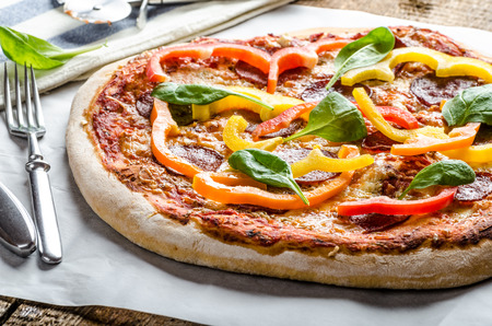 Rustic pizza with salami and peppers, spinach leaves photo