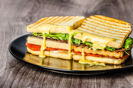 ham sandwich: Three floor Panini toast with bacon, arugula, pepperoni salami and hollandaise sauce Stock Photo