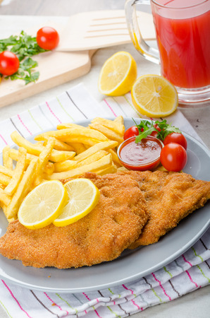 Schnitzel with french fries and a spicy dip, fresh from red orange Stock Photo - 34167256