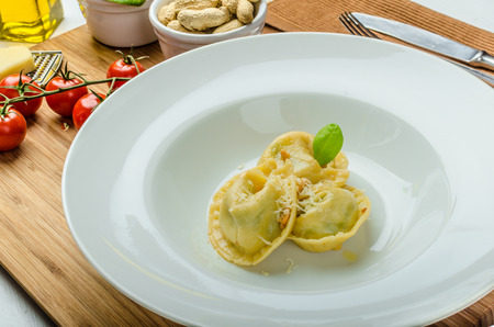 Homemade tortellini stuffed with spinach and garlic, topped with lightly buttered reduction with nuts photo