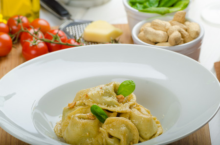 stuffed tortellini: Homemade tortellini stuffed with spinach and garlic, topped with lightly buttered reduction with nuts Stock Photo