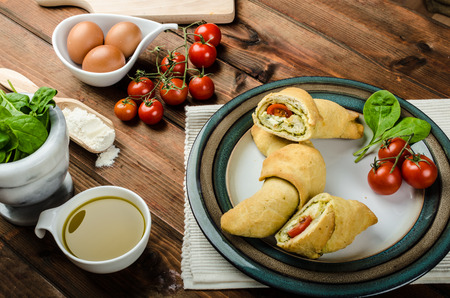 Home calzone rolls stuffed with cherry tomatoes, basil pesto and spinach with bio garlic photo