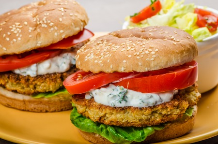 vegetarian hamburger: Vegetarian chickpea burger, tomato and dip of herbs, garlic and yogurt and salad with cherry tomatoes