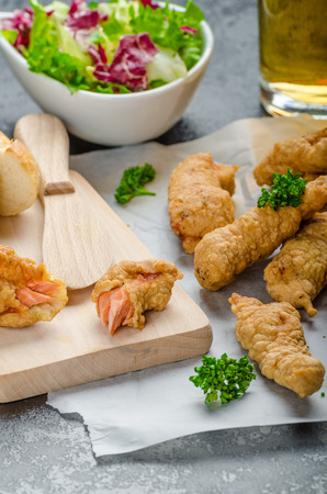escarola: Salm�n rebozado hierba con aderezo picante - pescado y patatas fritas sin patatas fritas gordas con ensalada mixta con escarola y la cerveza checa Foto de archivo