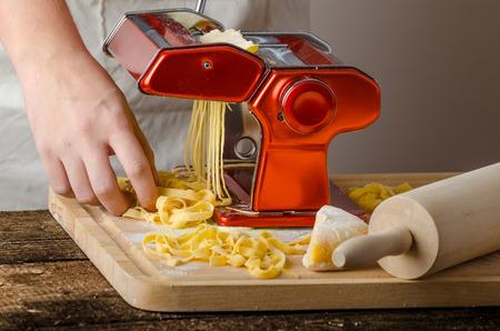 semolina paste: Produzione Chef pasta - Pasta grinder italiano, tavola di legno, mattarello, tutti a base di farina di semola Archivio Fotografico
