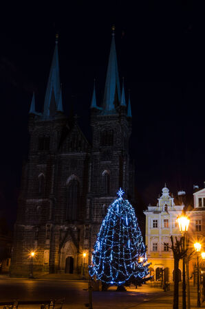 Christmas tree lit in the square, the church in the background photo