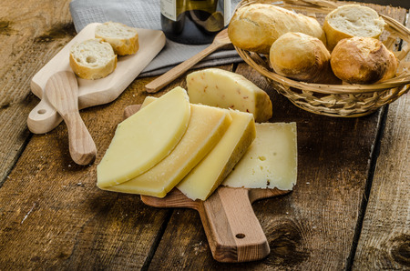 Delicious ripe cheese with crispy baguette and wine, wood board Standard-Bild