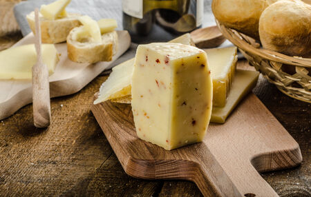 Delicious ripe cheese with crispy baguette and wine, wood board photo