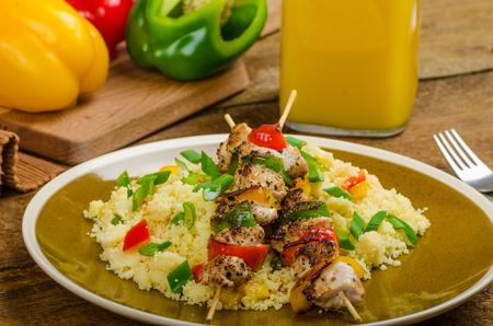 Couscous met groenten en lente-uitjes, kipspies met pepers Stockfoto