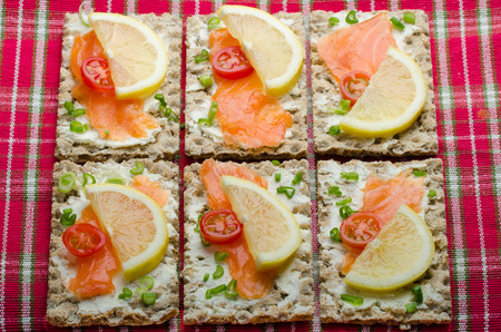 Bio healthy food - kneckebrot spread cheese with smoked salmon and cherry tomatoes photo