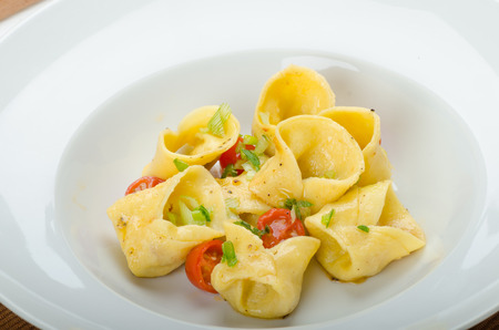 Homemade tortellini from semolina flour, stuffed with Parmesan cheese and tomatoes photo