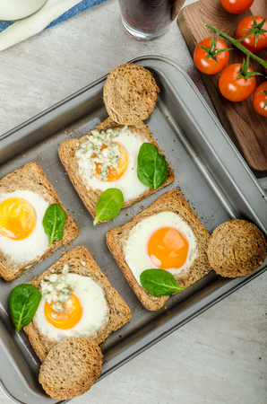 wheat toast: Baked Bulls-Eye Eggs on whole wheat toast with spinach and blue cheese on top