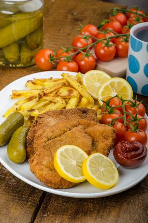 Big Chicken schnitzel with homemade chilli french fries, cherry tomatoes, pickels and grapes fresh photo