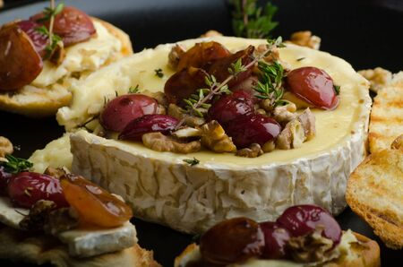 Brie cheese baked with nuts and grapes, tasty and crispy baguette and bio herbs, reduction of sugar, nuts and balsamic vinegar photo