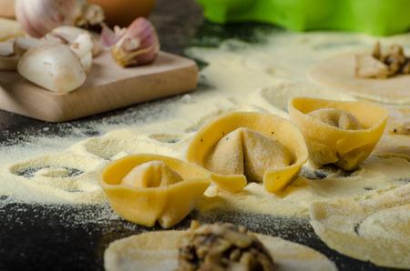 haciendo pan: Fabricaci�n de las pastas de s�mola de harina italiano, huevos bio, el ajo, las setas tortellini al final Foto de archivo