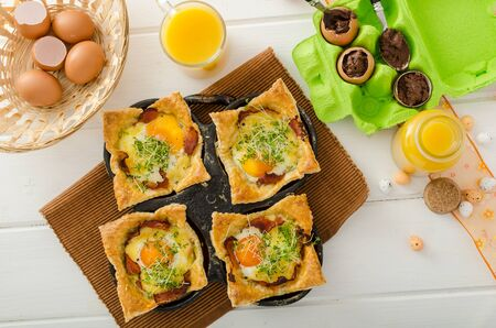 Fried eggs in puff pastry in ham, baked with cheese and topped with microgreens, fresh juice from oranges and eggs stuffed with chocolate photo