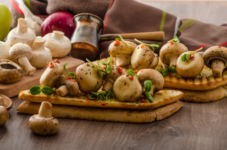 Wild mushrooms on baked toast with microgreens and chilli