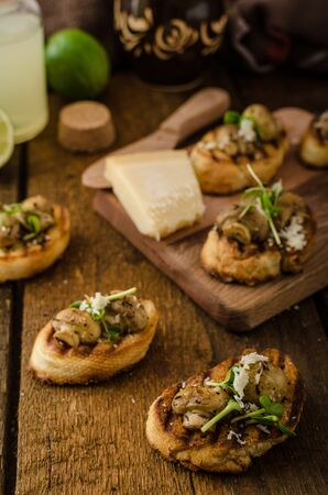 lime juice: Mushroom snacks on grilled baguette, topped with parmesan cheese and microgreens, fresh lime juice