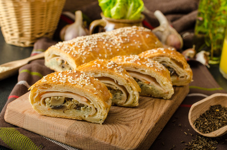 Roll out puff pastry stuffed with mushrooms, cheese and ham photo