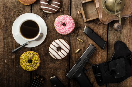 police officer: American police officer morning, donuts, juice, fresh black coffee and his gun