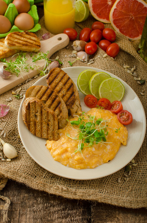 panini: Scrambled eggs, creamy and fluffy, panini toast, lime and tomato Stock Photo