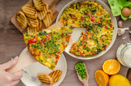 Vegetarian frittata with spinach, prosciutto and microgreens, baked baguette, served with woman hands
