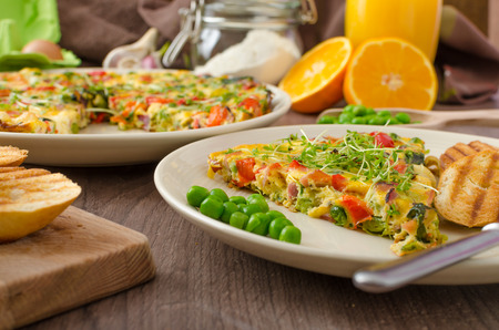 Vegetarian frittata with spinach, prosciutto and microgreens, fresh crispy baked baguette flavored with fresh pepper and olive oil