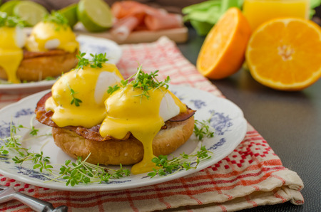 Eggs benedict, prosciutto topped with Hollandaise sauce photo