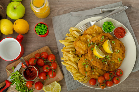 Schnitzel, french fries, cherry tomatoes and fresh microgreens pea salad photo