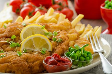 Schnitzel, french fries, cherry tomatoes and fresh microgreens pea salad Standard-Bild