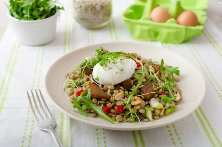 Healthy summer lentil salad with caramelized pear, arugula and poached egg soft on top photo