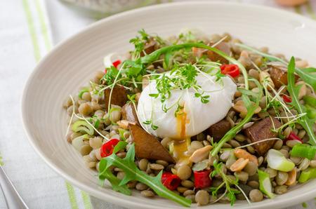 캐러멜 처리 된 배, arugula 및 위에 데친 달걀을 얹은 건강한 여름 렌즈 콩 샐러드