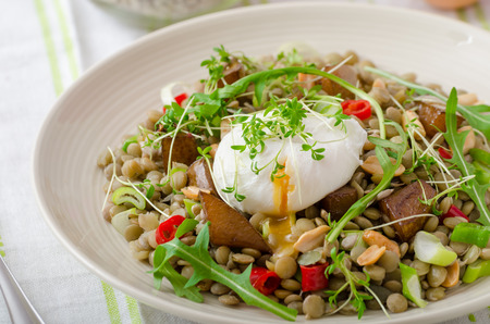 Healthy summer lentil salad with caramelized pear, arugula and poached egg soft on top Imagens - 38132363