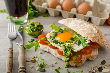 Ciabatta with fried egg, tomatoes and pesto, bio eggs and arugula for bio healthy photo