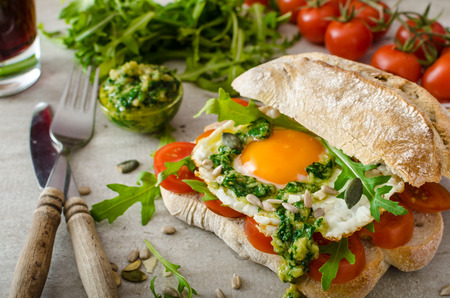 Ciabatta with fried egg, tomatoes and pesto, bio eggs and arugula for bio healthy photo