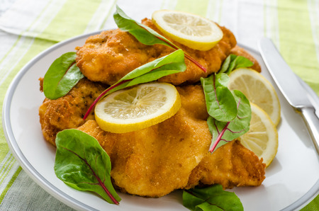 Fried veal fillet with arugula, lemon and spinach photo