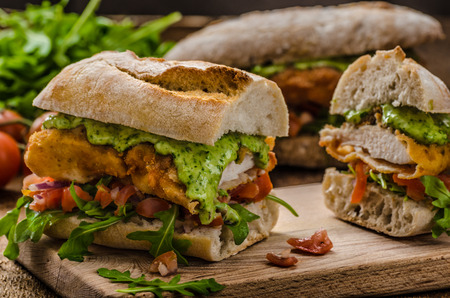 Veal schnitzel - fillet in a bun, with herb mayonnaise, tomato salsa and fresh herbs photo