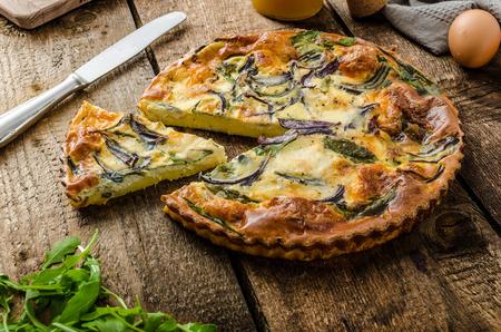 Polenta quiche met rode ui, spinazie, mozzarella en rucola Stockfoto