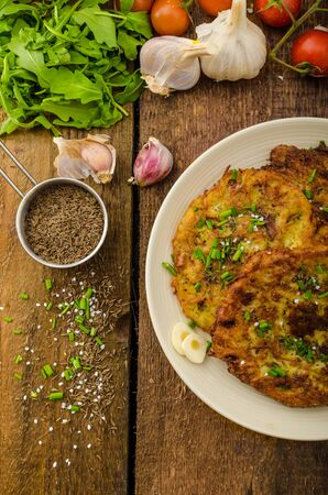 Fried potato pancakes with garlic and marjoram, sprinkled cumin, chive and coarse-grained salt photo