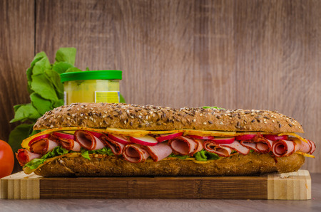 Rustic lined wholemeal baguette with smoked rump, spicy cheese and vegetables