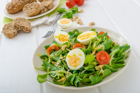 Lambs lettuce salad with roated cashews, sunflower nuts, pumpkin nuts, boiled eggs on top, healthy bread photo
