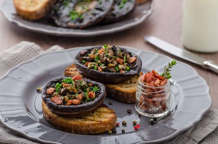 portobello: Portobello stuffed with herbs, bacon and garlic, delicacyon toasted crusty garlic bread Stock Photo