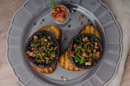 crusty: Portobello stuffed with herbs, bacon and garlic, delicacyon toasted crusty garlic bread Stock Photo