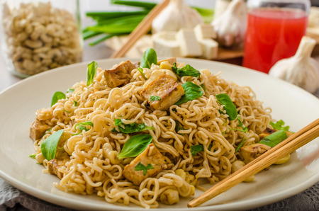 Chinese noodles with tofu and cashew nuts, with garlic, fresh salad on top Foto de archivo