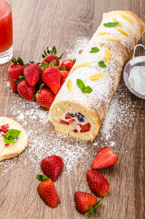 suger: Sponge roll with strawberries and blueberries, all fresh fruit, sprinkled suger with mint leafes Stock Photo
