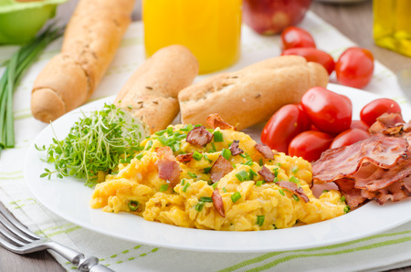 Scrambled eggs with bacon, chive and tomatoes, fresh juice and little microgreens healthy salad Stock Photo
